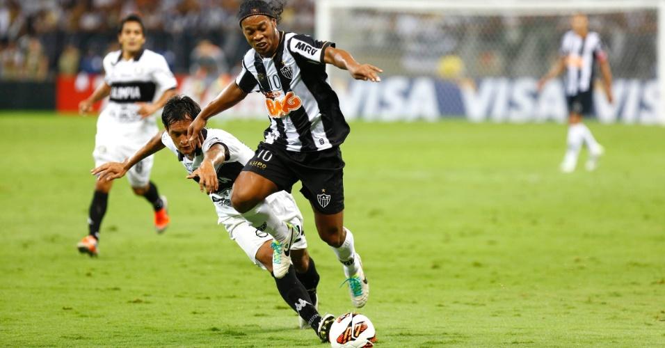 24.07.2013 - Ronaldinho Gaúcho pula em disputa de bola com jogador do Olimpia