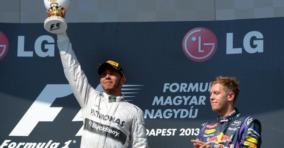 Observado pelo terceiro colocado Vettel, Lewis Hamilton celebra vitória no GP da Hungria, sua primeira no ano e a quarta em Budapeste