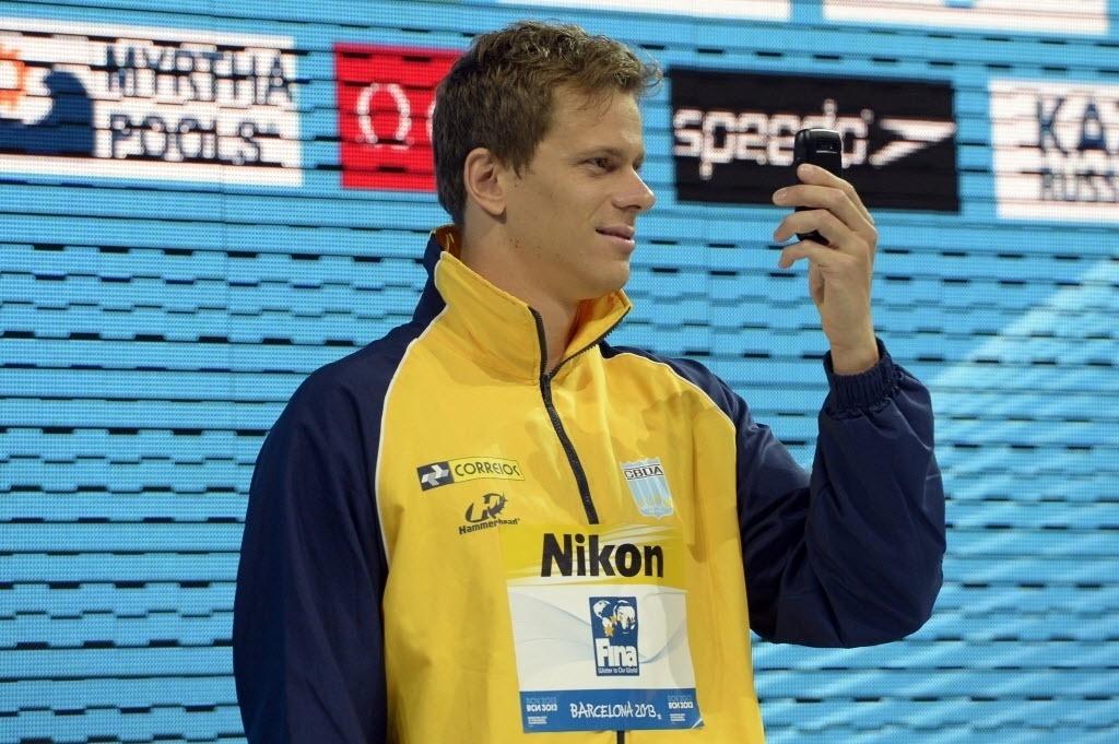 29.jul.2013 - Cesar Cielo tira foto durante cerimônia de premiação dos 50 m borboleta; brasileiro ganhou a medalha de ouro