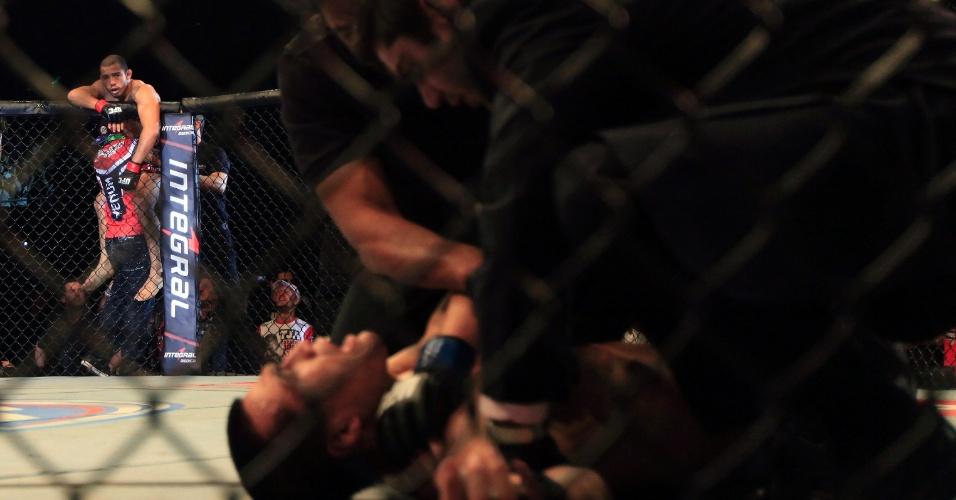 04.ago.2013 - Após saltar a grade, José Aldo observa o sofrimento do Zumbi Coreano, que grita de dor por uma lesão no ombro no fim do combate no Rio