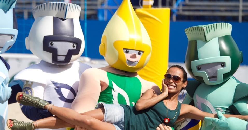20.jul.2011 - Torcedora posa com os mascotes dos Jogos Militares durante o jogo de vôlei feminino entre Brasil e Lituânia
