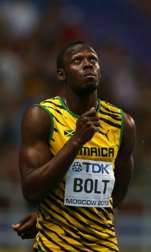 11.ago.2013 - Jamaicano Usain Bolt brinca estar usando um guarda-chuva antes da prova dos 100m do Mundial de Moscou