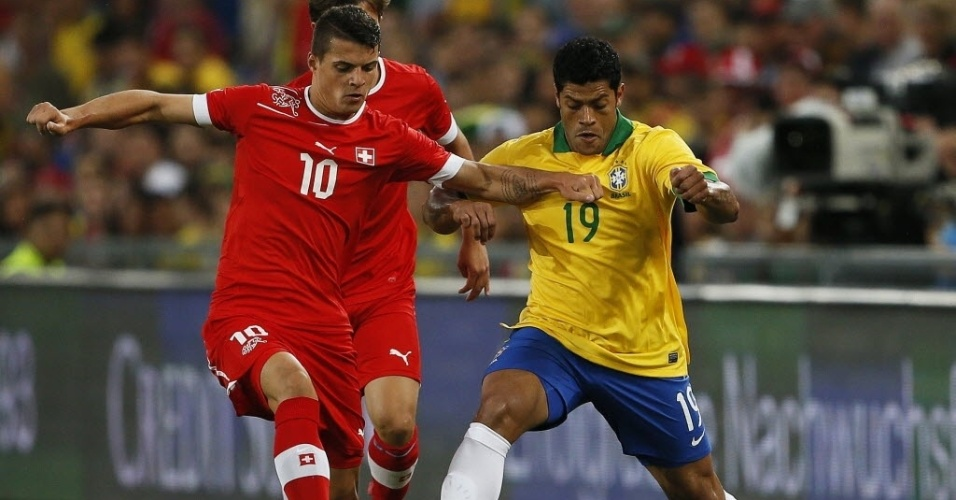 14.ago.2013 - Hulk e Granit Xhaka correm pela bola durante amistoso entre Brasil e Suíça na Basileia