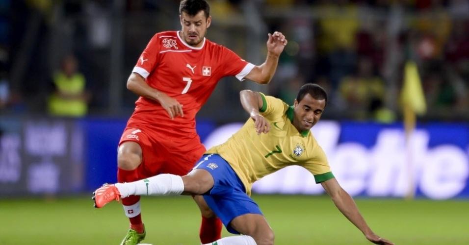 14.ago.2013 - Lucas disputa bola com Tranquillo Barnetta durante amistoso entre Brasil e Suíça