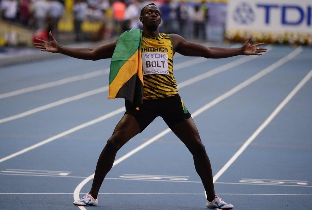 17.ago.2013 - Usain Bolt faz pose com a bandeira da Jamaica após levar o ouro nos 200 m