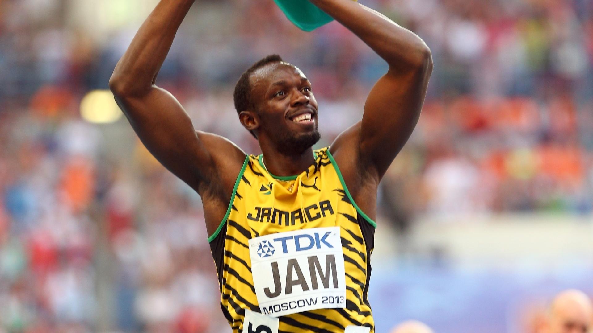 18.ago.2013 - Usain Bolt sorri com a bandeira da Jamaica para comemorar o ouro no revezamento 4x100 m