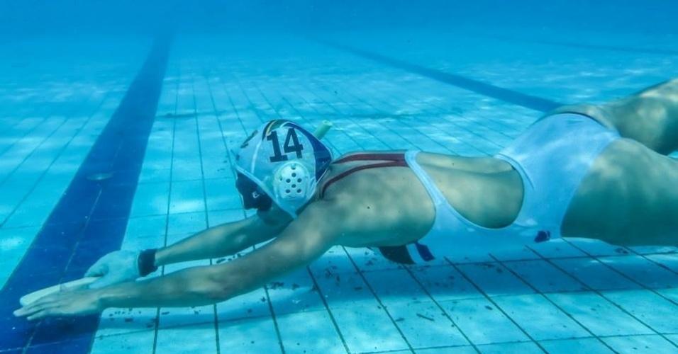 Atleta tenta conduzir o disco com seu pequeno taco no hóquei subaquático