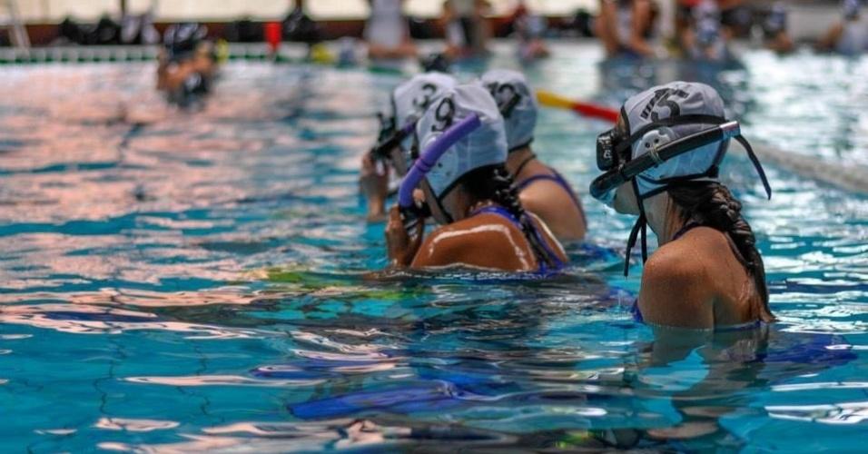 Atletas do hóquei subaquático saem da piscina para respirar