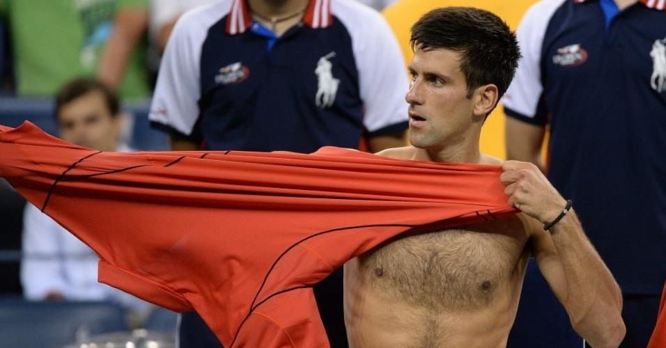27.ago.2013 - Novak Djokovic troca de camiseta durante partida de estreia no Aberto dos EUA contra Ricardas Berankis