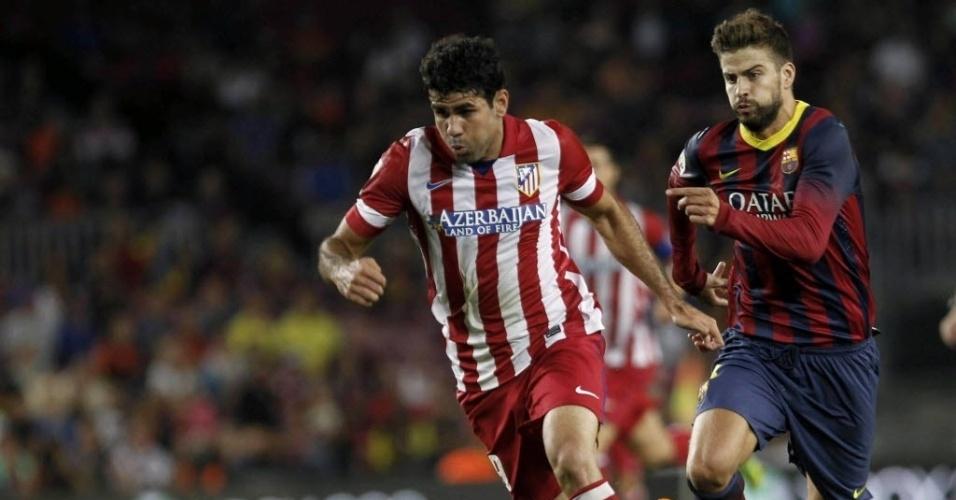28.ago.2013 - Gerard Piqué corre atrás do brasileiro Diego Costa na partida da Supercopa da Espanha
