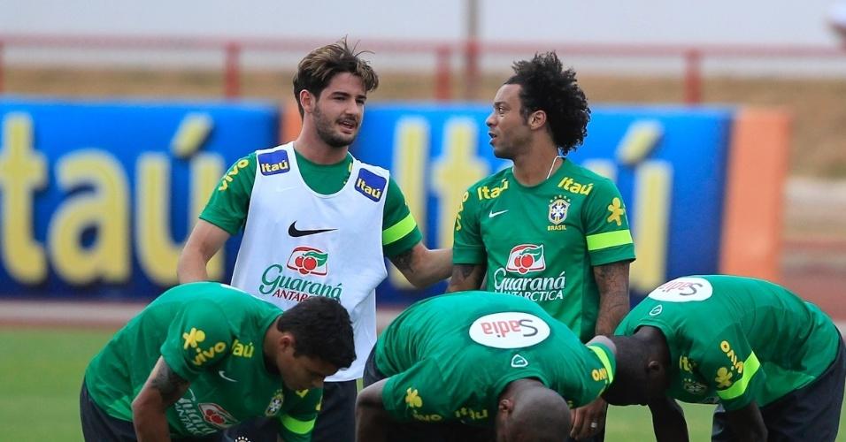 04.09.2013 - Alexandre Pato e Marcelo conversam enquanto os outros jogadores fazem alongamento durante o treino da seleção brasileira em Brasília
