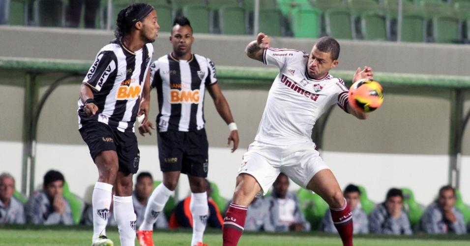 04.set.2013 - Observado por Fernandinho, Ronaldinho tenta o passe em partida contra o Fluminense