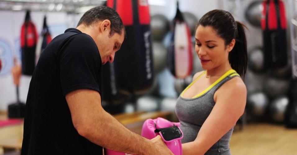 09.09.2013 - Personal de Maria ajeita as luvas de boxe nas mãos de Maria Melilo para treino em academia