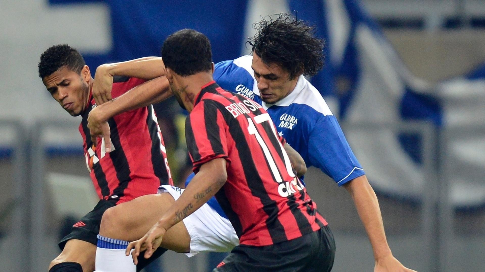 14.set.2013 - Ricardo Goulart, do Cruzeiro, tenta ganhar dividida de dois atletas do Atlético-PR