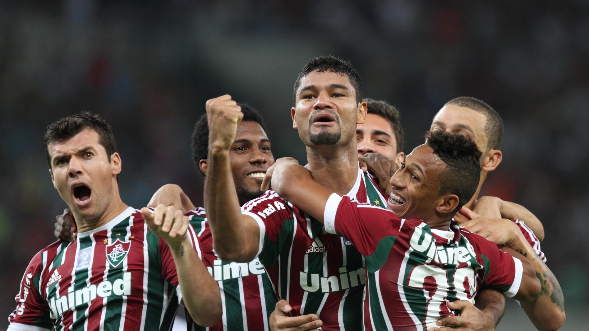 21.set.2013 - Gum, zagueiro do Fluminense, é abraçado pelos companheiros na comemoração do seu gol na partida contra o Coritiba