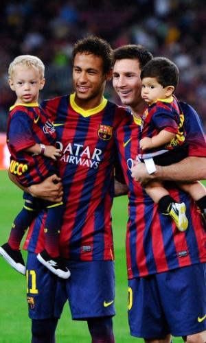 24.set.2013 - Neymar entra no gramado e posa para foto com o filho Davi Lucca ao lado de Messi com o filho Thiago