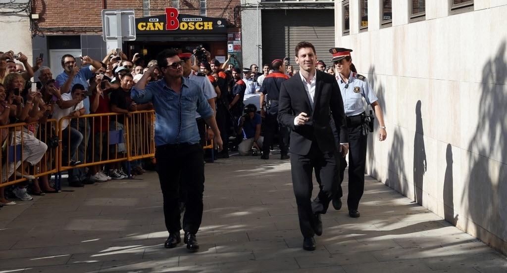 27.set.2013 - Com o local cercado por fãs e fotógrafos, Lionel Messi chega ao tribunal em que responderá ao processo por fraude fiscal