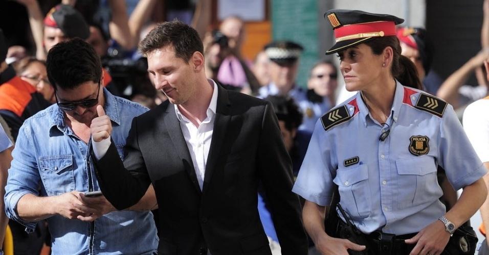 27.set.2013 - Messi faz sinal de positivo ao ser acompanhado por policial ao chegar no tribunal em que responderá por fraude fiscal na Espanha