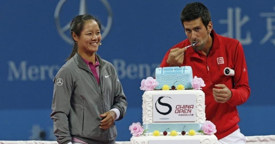27.set.2013 - Na Li dá risada enquanto Novak Djokovic come bolo antes de amistoso entre ambos na China