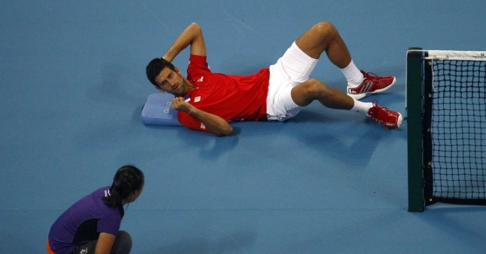27.set.2013 - Novak Djokovic brinca com pegadora de bola e deita em quadra durante amistoso na China contra Na Li