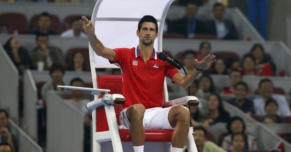 27.set.2013 - Novak Djokovic brinca na cadeira de arbitragem durante partida-exibição contra Na Li na China
