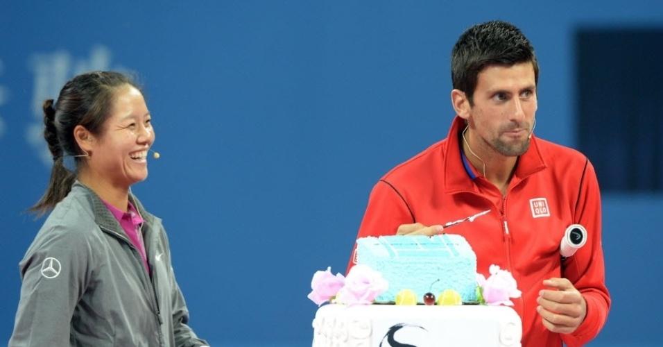 27.set.2013 - Novak Djokovic come pedaço de bolo antes de partida-exibição contra Na Li em Xangai