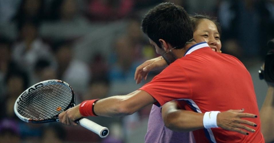 27.set.2013 - Novak Djokovic e Na Li se abraçam após amistoso disputado em Xangai, para promover o Masters 1000 local