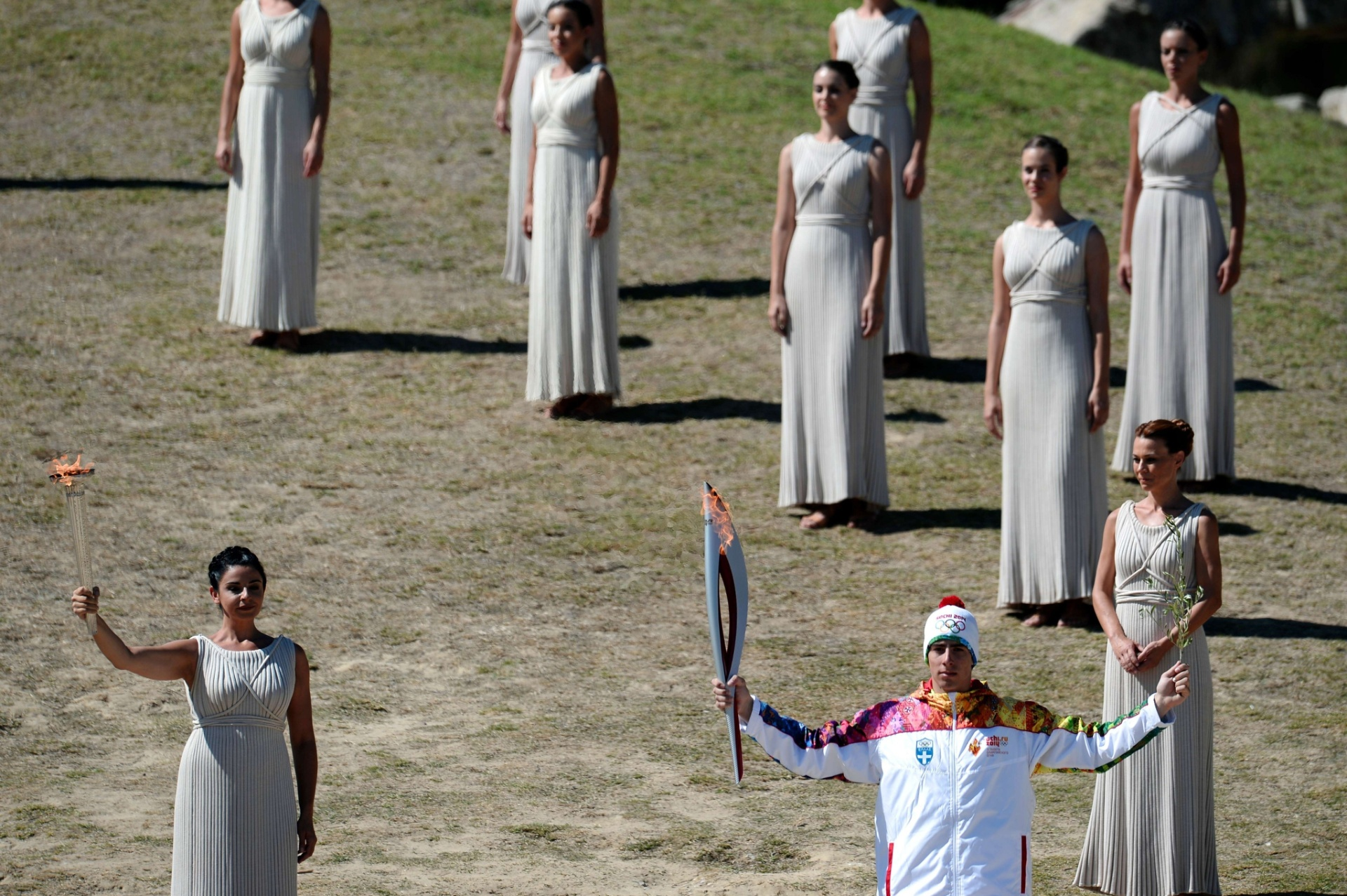 29.set.2013 - O esquiador grego, Giannis Antonou recebe a tocha e o ramo de oliva da sacerdotisa