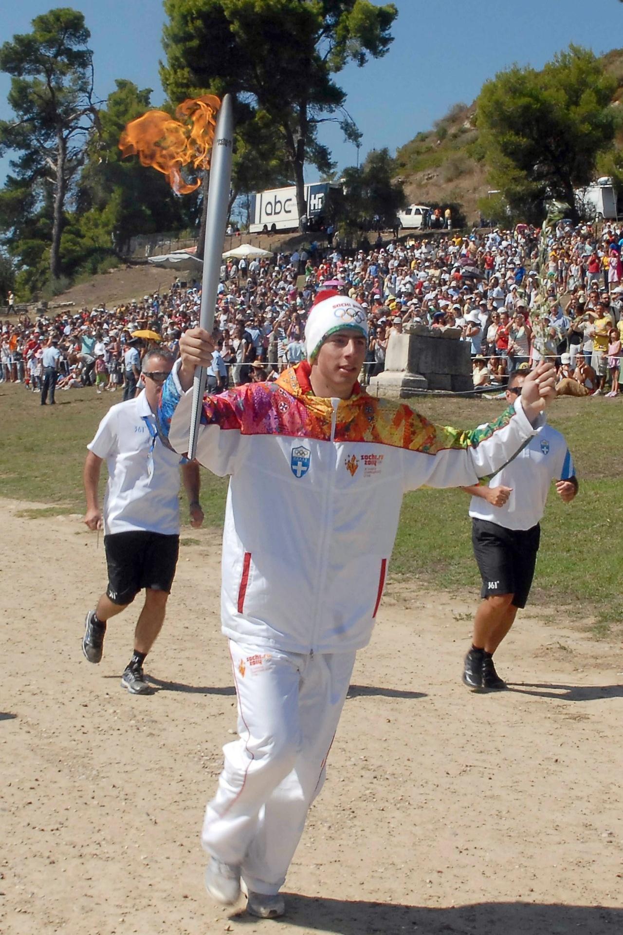 29.set.2013 - O esquiador grego, Yiannis Antoniou, foi o primeiro a carregar a tocha após cerimônia