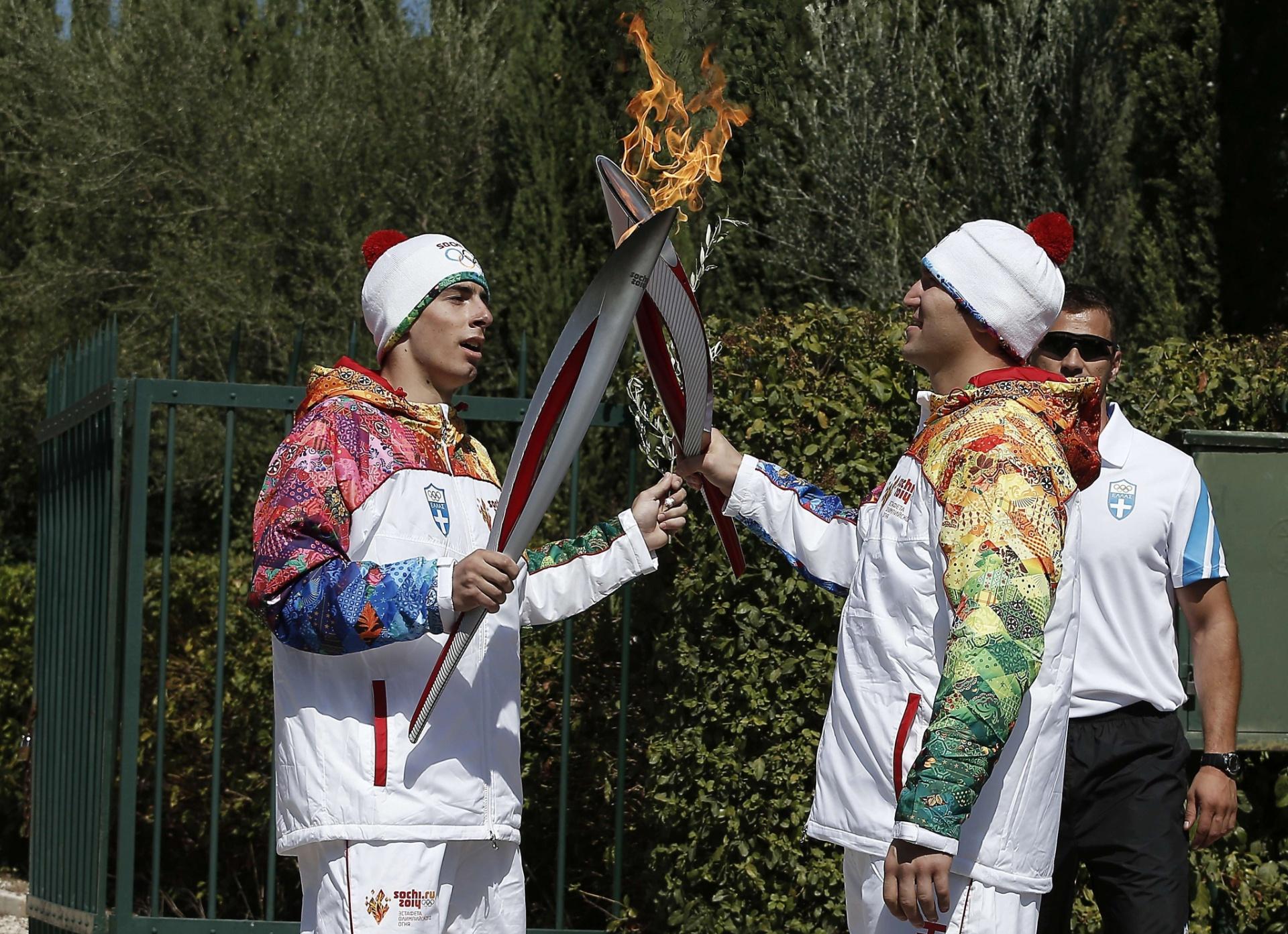 29.set.2013 - Perto do monumento Pierre de Coubertin, Giannis Antoniou passa a chama para o esquiador russo Alexander Ovechkin