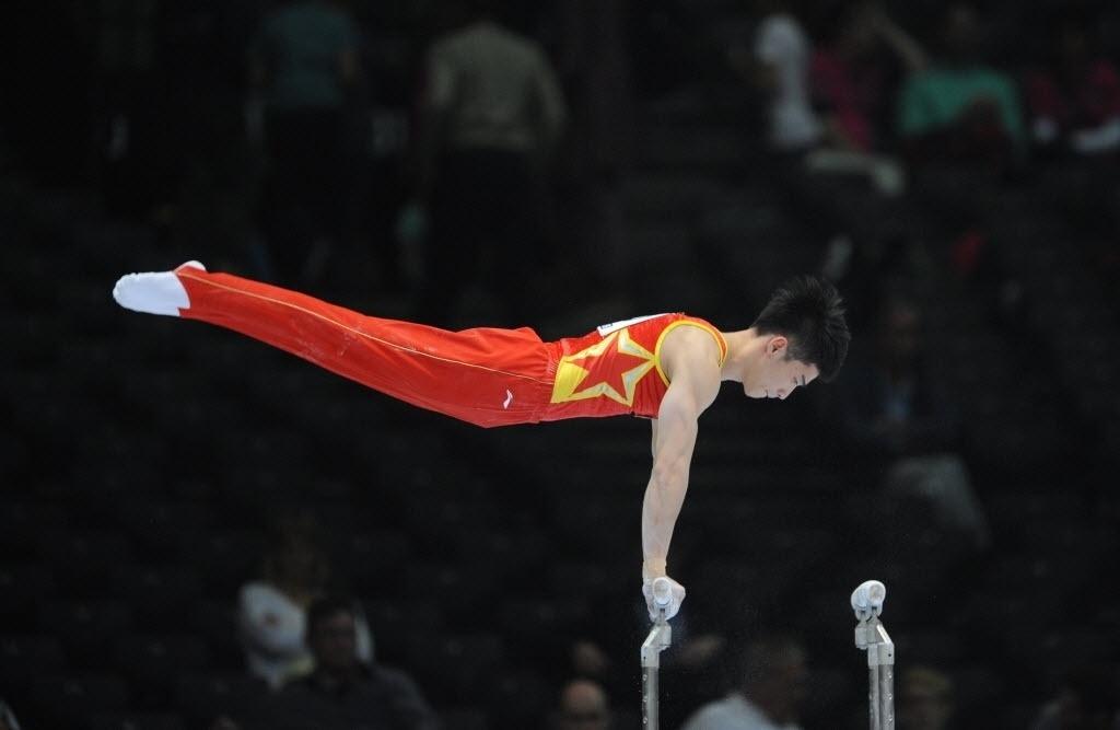 30.09.2013 - Chinês Shixiong Zhou faz sua série nas barras durante as eliminatórias do individual geral