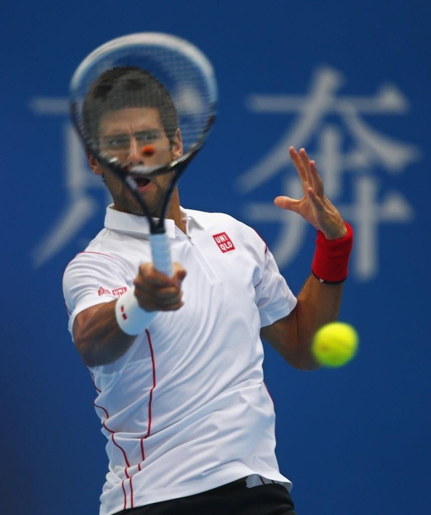 01.out.2013 - Novak Djokovic rebate bola durante a estreia em Pequim contra Lukas Rosol
