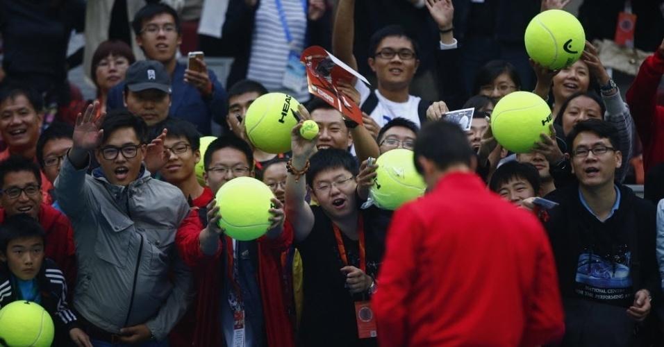 03.out.2013 - Novak Djokovic autografa objetos para a torcida chinesa após avançar para as quartas em Pequim