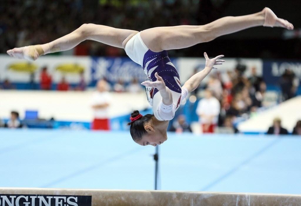 04.10.2013 - Jinnan Yao, da China, executa sua série na trave durante a final do individual geral no Mundial da Antuérpia