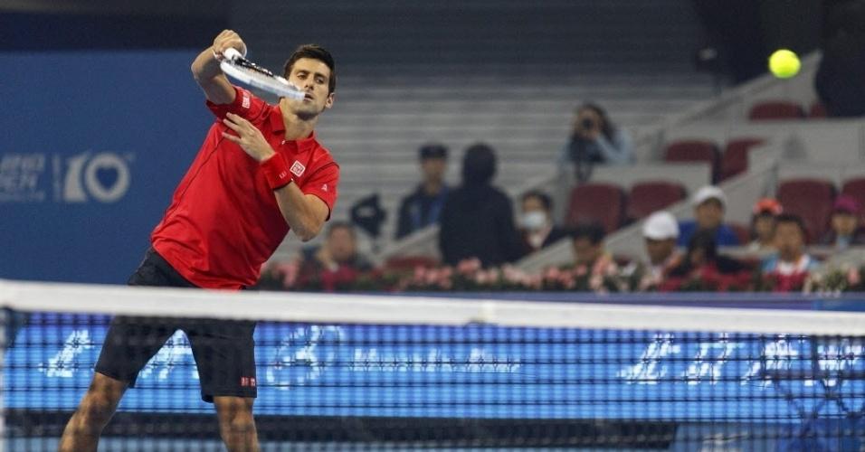 04.out.2013 - Novak Djkovic dá voleio na rede durante o confronto contra Sam Querrey