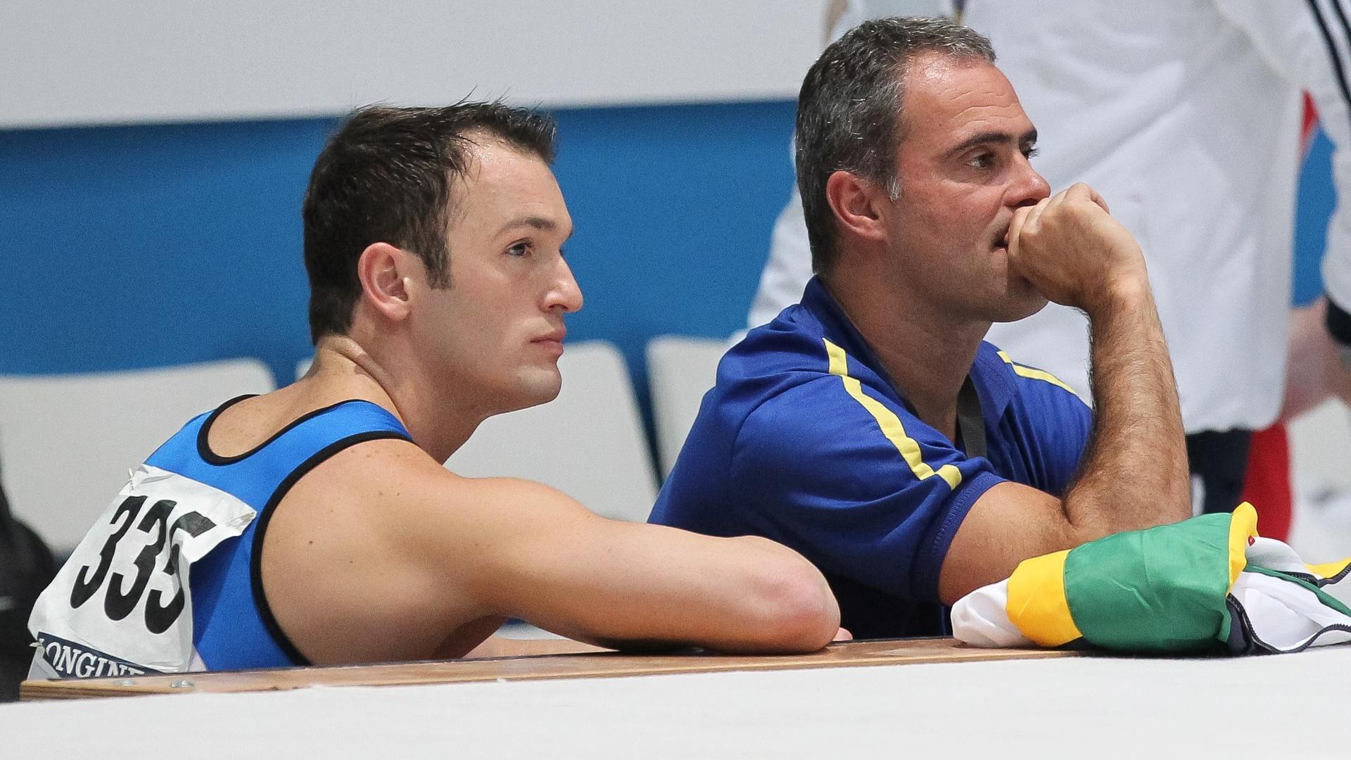 05.10.2013 - Diego Hypolito fica com cara fechada ao lado de seu técnico após sua apresentação no solo