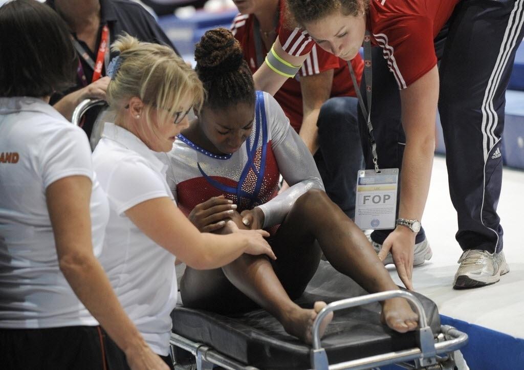 05.10.2013 - Ginasta holandesa Chantysha Netteb é retirada na maca após lesionar o joelho na final do salto no Mundial