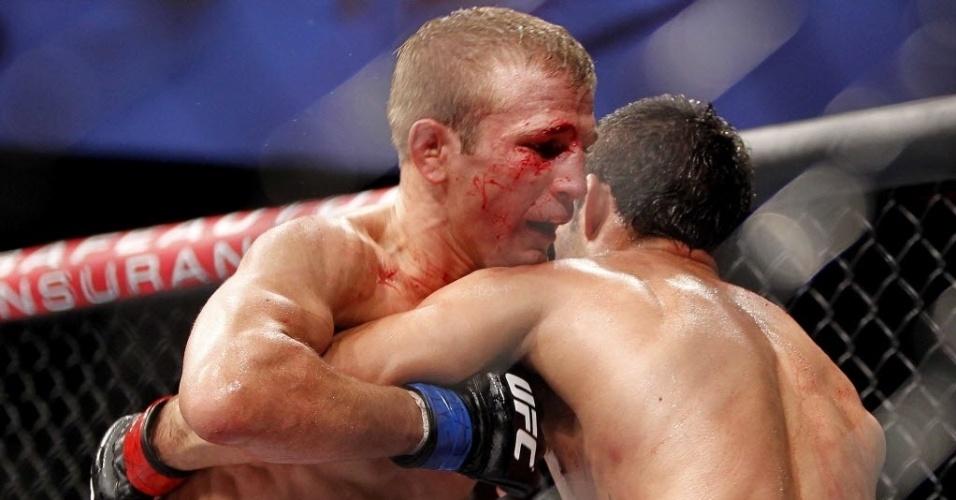 Sangrando, o americano TJ Dillashaw abraça o brasileiro Raphael Assunção (dir.) na luta pela categoria peso-galo do UFC Barueri