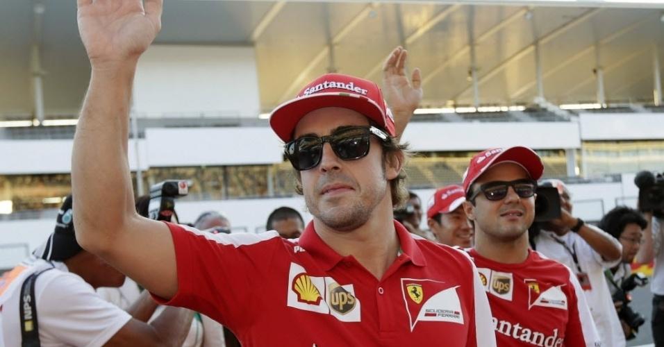 10.out.2013 - Fernando Alonso acena para fãs no Japão ao chegar em Suzuka; ao seu lado, Felipe Massa
