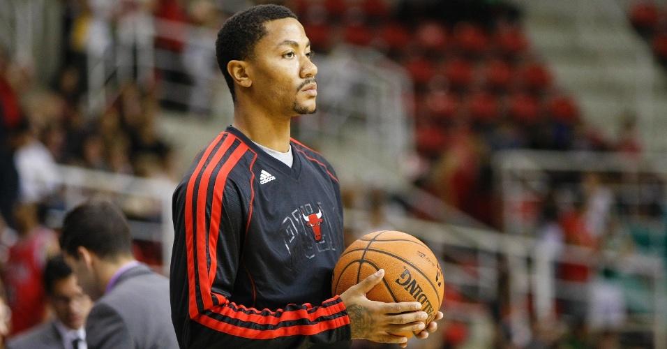 12.10.2013 - Derrick Rose, astro dos Bulls, observa seus companheiros do lado de fora da quadra; o jogador não será utilizado