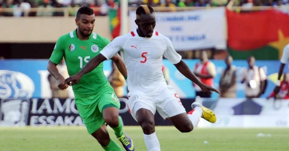 12.ou.2013 - Mohamed Koffi (d), de Burkina Fasso, tenta jogada contra a Argélia em duelo válido pelas Eliminatórias para a Copa do Mundo de 2014