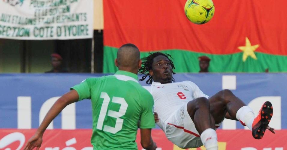 12.out.2013 - Koulibaly, de Burkina Faso, tenta bicicleta em partida contra a Algeria pelas Eliminatórias Africanas da Copa do Mundo 2014