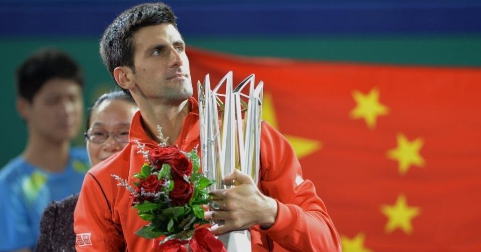 13.out.2013 - Novak Djokovic posa com as flores e o troféus que ganhou após conquistar Xangai