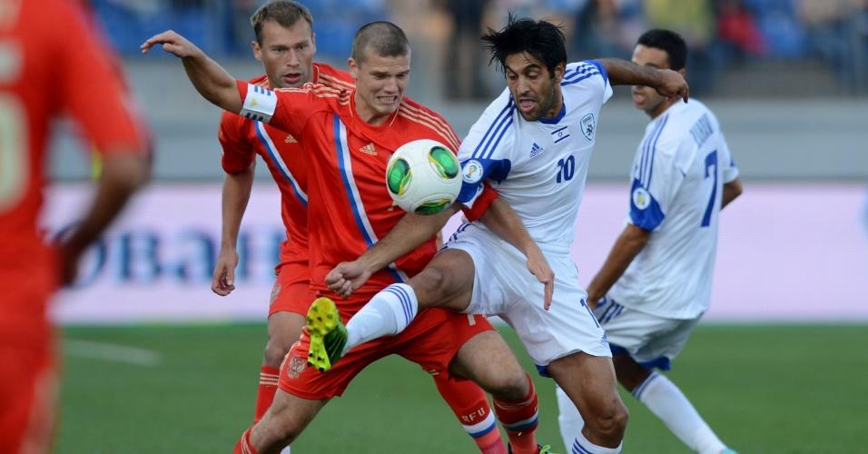 10.set.2013 - Igor Denisov (e), da Rússia, disputa jogada com Elyaniv Barda, de Israel, em partida pelas eliminatórias da Copa-2014; russos ganharam por 3 a 1
