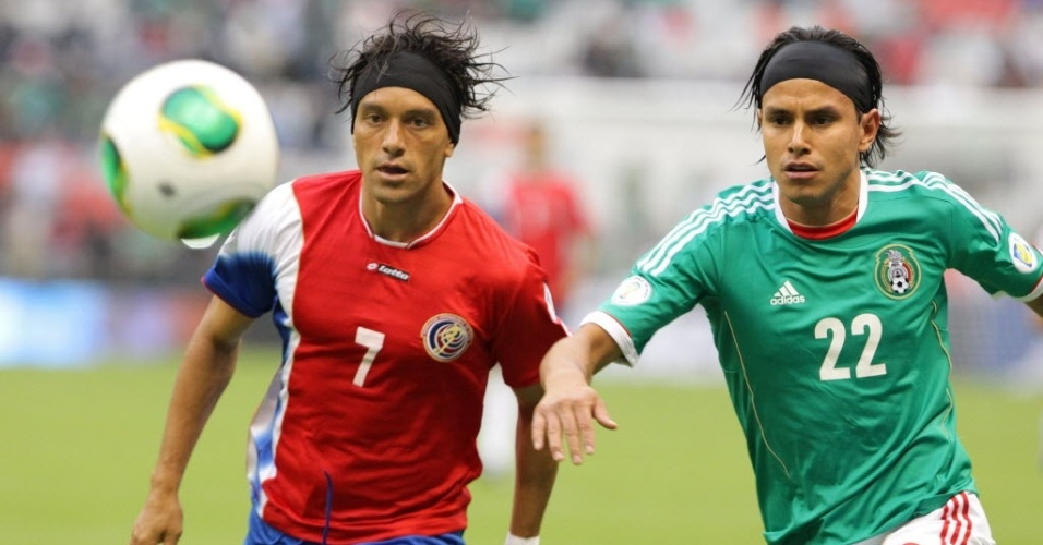 11.jun.2013 - Christian Bolaños (e), da Costa Rica, disputa jogada com o mexicano Gerardo Flores em partida das eliminatórias da Copa-2014
