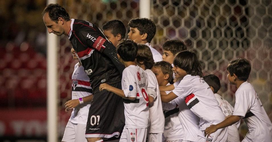 16.out.2013 - Rodeado por crianças, Rogério Ceni entra em campo para jogo contra o Náutico
