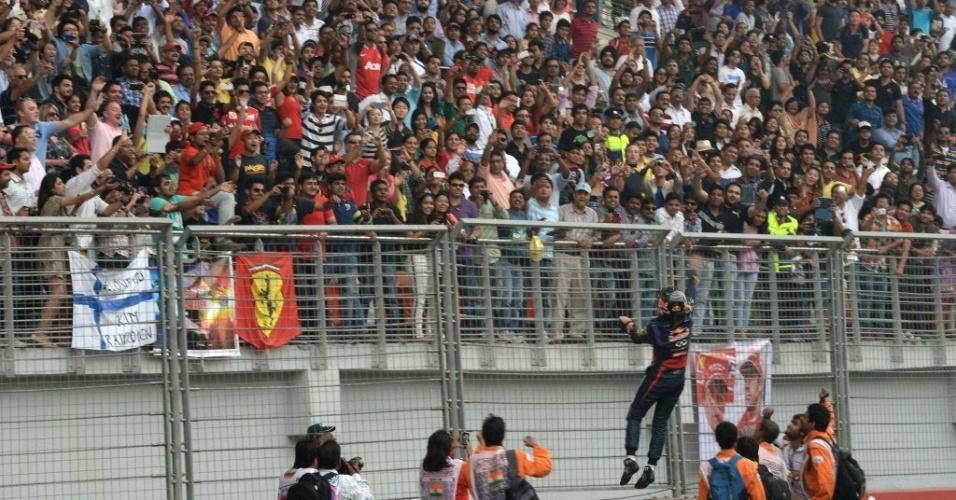 27.out.2013 - Sebastian Vettel pula na grande das arquibancadas do autódromo de Buddh para celebrar o tetracampeonato mundial de F-1