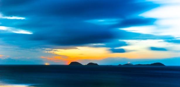 Imagem de pôr do sol na praia a partir da areia com lentes teleobjetivas criando perspectivas de cores e nuances em trabalho de característica própria do fotógrafo