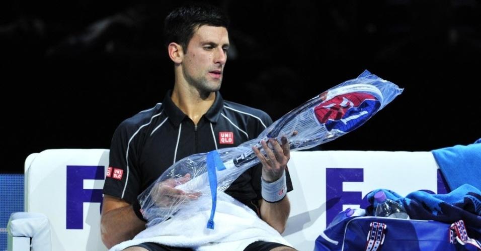 07.nov.2013 - Novak Djokovic troca de raquete durante a partida contra Juan Martin Del Potro pelas Finais da ATP
