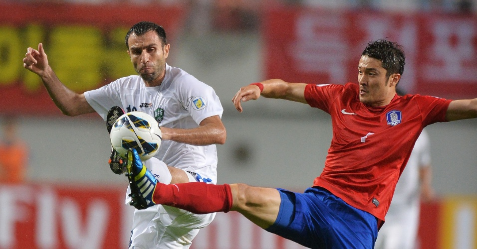 11.jun.2013 - Park Jongwoo (d), da Coreia do Sul, tenta dominar a bola mesmo sob a marcação de Timur Kapadze, do Uzbequistão, em partida pelas eliminatórias da Copa do Mundo-2014